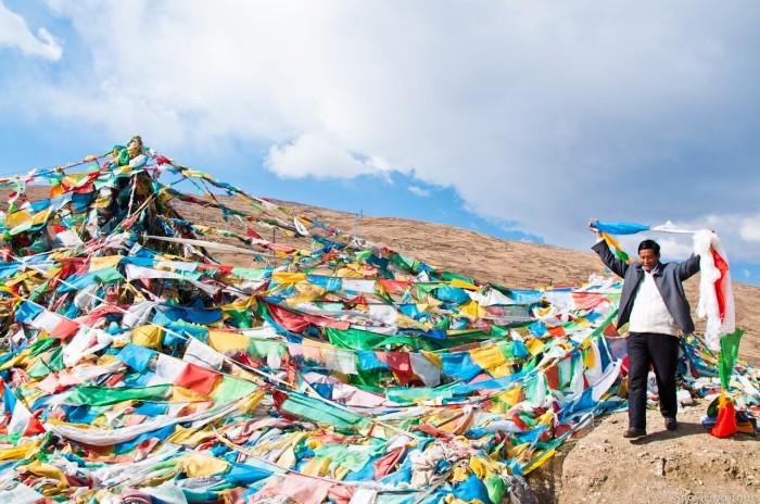мужчина развешивает молитвенные флажки на перевале после г. Шигатце
