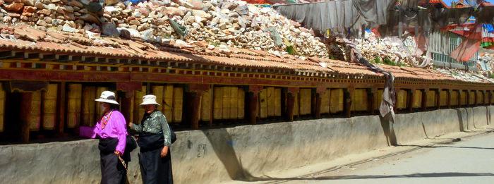Two pilgrims circumambulate the Mani Stone Pile in Jyekundo, Kham