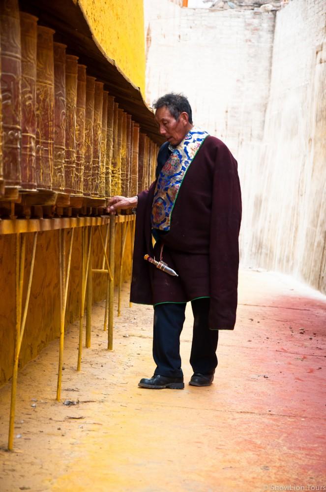 тибетец крутит молитвенные барабаны в монастыре Ронгву