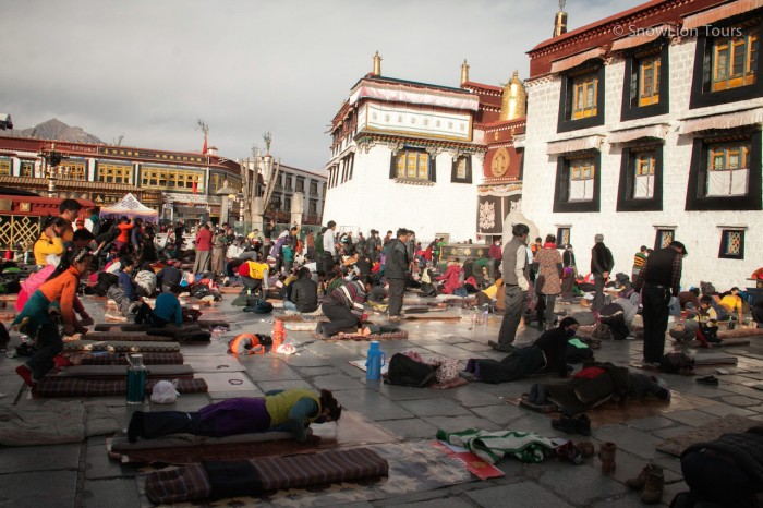 тибетские паломники выполняют простирания перед входов в Джокханг
